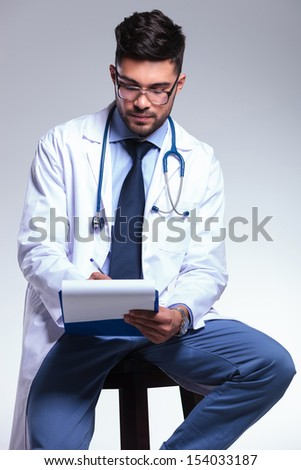 young male doctor sitting on a stool and taking notes on his clipboard. on gray background - stock photo