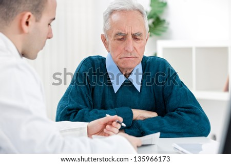 Young male doctor talking with senior patient - stock photo