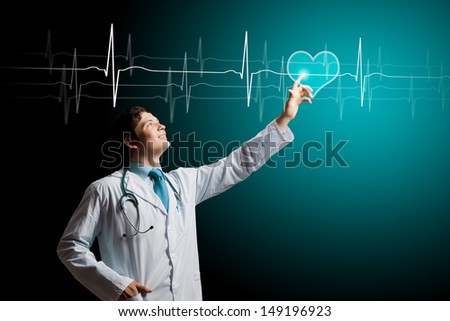 Young male doctor touching digital lightened image - stock photo