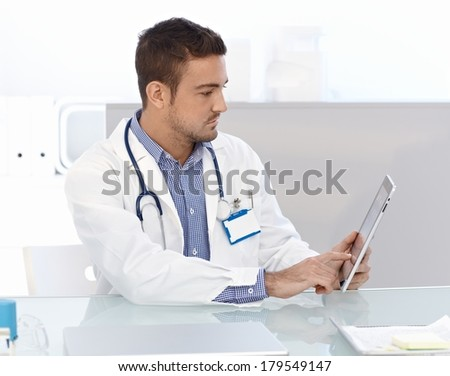 Young male doctor using tablet computer, sitting at desk in doctor's room. - stock photo