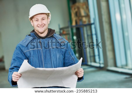 young male engeneer worker foreman at a indoors building site with blueprints - stock photo