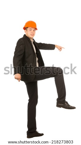 Young Male Engineer in Black Coat and Orange Helmet Lifting One Leg Position. Emphasizing Going Up Using Stairs. Isolated on White Background. - stock photo