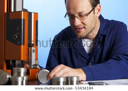 Young male engineer in blue overall taking precision measurement of metal parts with micrometer, isolated on blue background. - stock photo