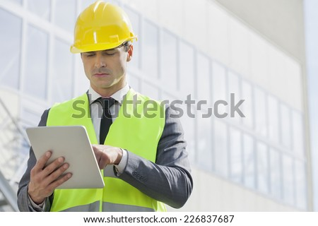 Young male engineer using digital tablet outside industry - stock photo