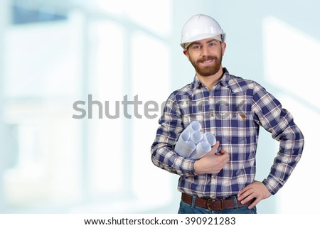 Young male engineer with helmet holding blueprints - stock photo