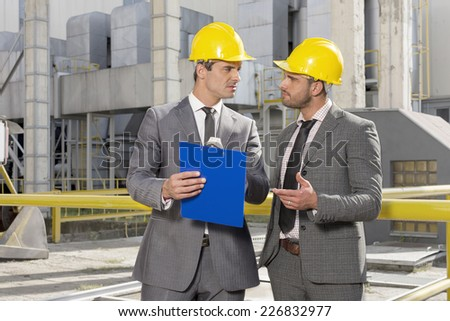 Young male engineers with clipboard discussing at construction site - stock photo