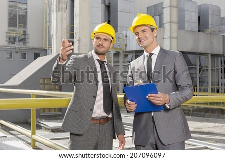 Young male engineers with clipboard discussing outside industry - stock photo