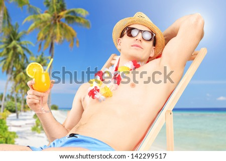 Young male enjoying on a tropical beach, lying on a sunbed and holding a cocktail - stock photo
