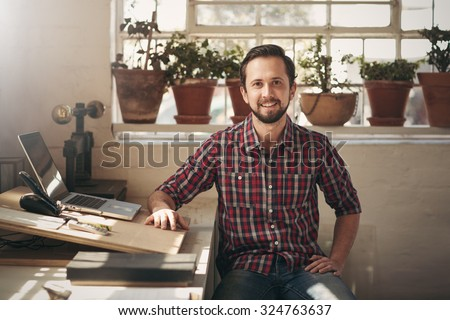 Young male entrepreneur sitting in the office space of his design studio looking confidently at the camera - stock photo