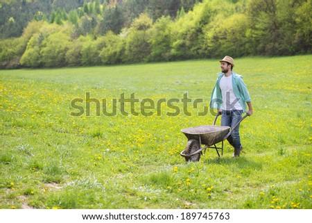 Young male farmer pushing wheelbarrow in the field - stock photo