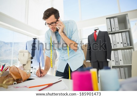 Young male fashion designer working on his designs while on call in the studio - stock photo