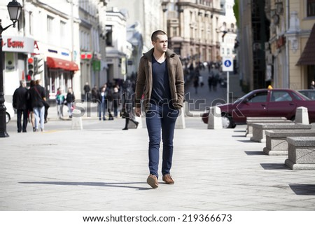 Young male fashion model walking in street  - stock photo