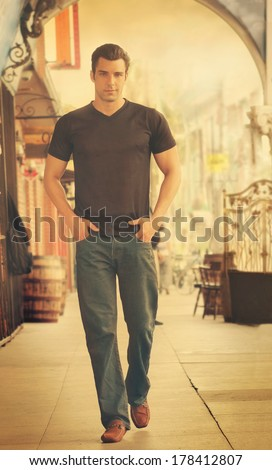 Young male fashion model walking in street scene with retro vintage toning - stock photo