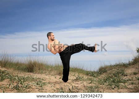 young male fighter exercising on a sand hill - stock photo