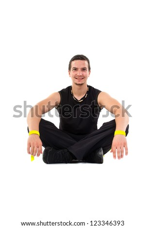 Young male fitness teacher sitting on floor - stock photo