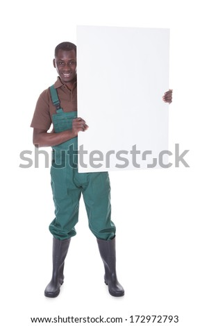 Young Male Gardener Holding Bill Board Over White Background - stock photo