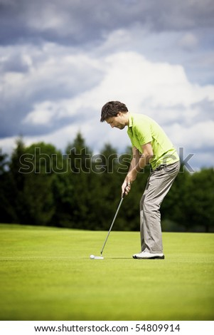 Young male golf player putting a golf ball on the green. - stock photo