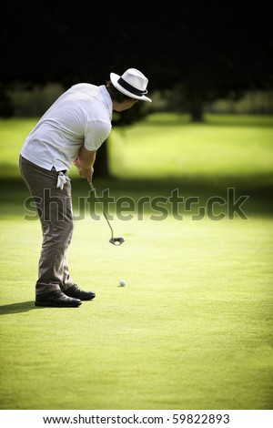 Young male golf player putting on green with dark forest in the background, usable as free space for text. - stock photo