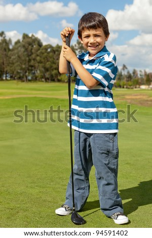 Young male golf player standing at the field with a golf-club - stock photo