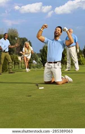 Young male golfer kneeling happy at hole after successful putt, shouting happy with hands fisted. - stock photo