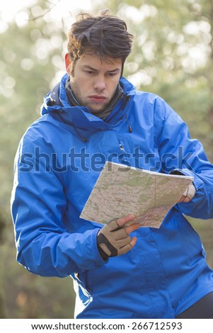 Young male hiker reading map in forest - stock photo