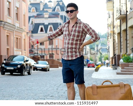 Young male hitchhiker standing with his suitcase in an urban street thumbing a lift - stock photo