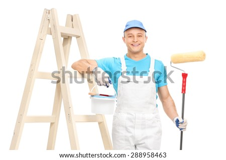 Young male house painter in a white clean jumpsuit holding a paint roller and leaning on a wooden ladder isolated on white background - stock photo