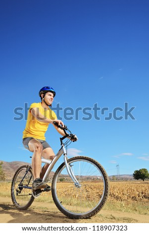 Young male in yellow shirt riding a bike on a sunny day, Macedonia - stock photo