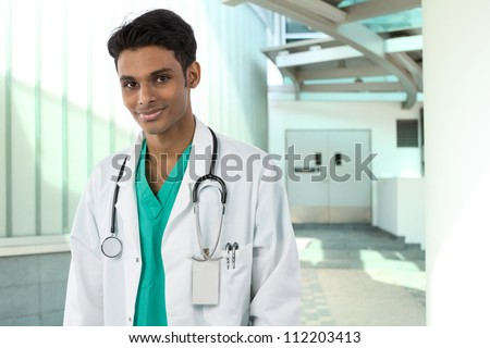 Young Male Indian doctor wearing a white coat and stethoscope. Standing outside a hospital. - stock photo