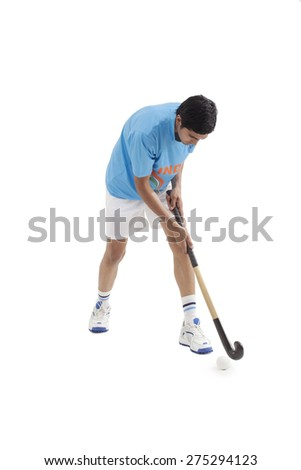 Young male Indian player playing hockey isolated over white background - stock photo