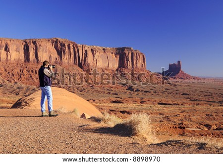 Young male is photographing Monument Valley Tribal Park, Navajo Nation, Utah - stock photo