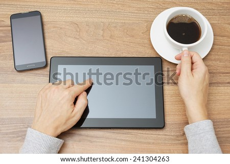 young male is using tablet pc and drinking coffee - stock photo
