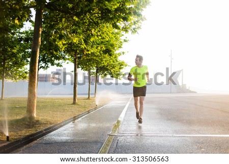 Young male jogger running on the road along beautiful green park while listen to music in headphones on his smart phone, male sports structure runs outdoors in sunny morning while using modern device - stock photo
