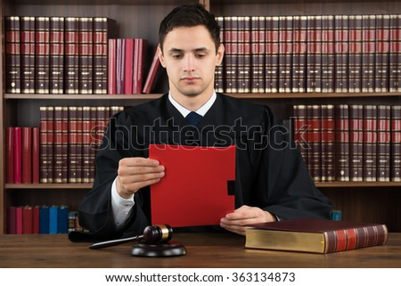 Young male judge reading legal document at desk in courtroom - stock photo