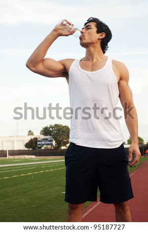 Young male latino athlete drinking water - stock photo