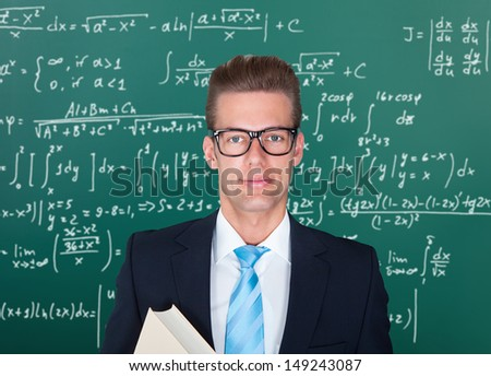 Young Male Lecturer Standing In Front Of Chalkboard - stock photo