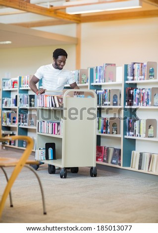 Young male librarian with trolley books in library - stock photo