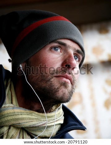 Young male listening to music with earphones - stock photo