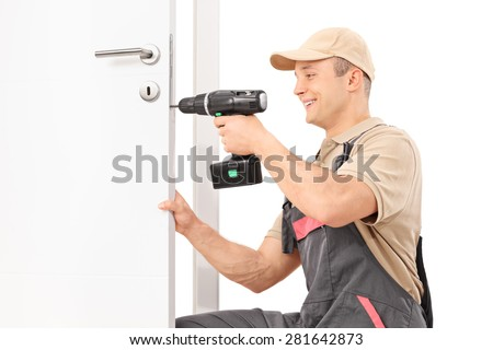 Young male locksmith screwing a screw on a lock of a door with a hand drill isolated on white background - stock photo