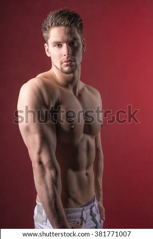 Young male model against red background - Handsome undressed male looking into camera - Sexy shirtless guy - Shirtless male model wearing jeans - Fit muscular male - Athletic young man in jeans - Hair - stock photo