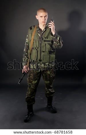 Young male model in military outfit and military attributes posing in studio on black - stock photo