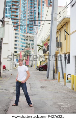 Young male model posing in an alley in Miami Beach - stock photo