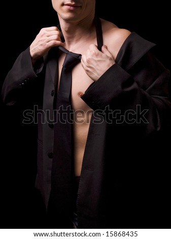young male model posing in black shirt and tie - stock photo