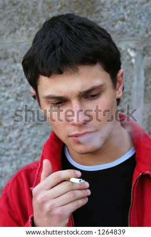 Young male model smoking a cigarette - stock photo