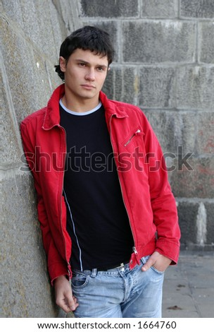 Young male model waiting for somebody next to the stonewall - stock photo