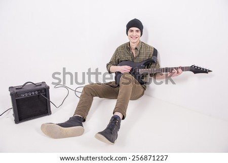 Young male musician is playing a six-string bass guitar in studio with amp. - stock photo