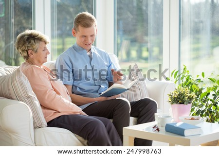 Young male nurse reading the book to his older ward - stock photo