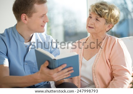 Young male nurse spending his free time with elderly woman - stock photo