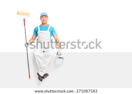 Young male painter sitting on a blank signboard and holding a paint roller and a color bucket isolated on white background - stock photo
