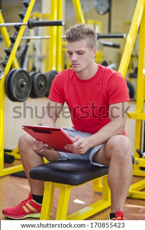 Young male personal trainer writing on clipboard, with training equipment behind him in gym - stock photo